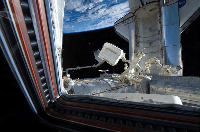 Figure 22 - Il trasferimento di AMS-02, tramite il Canadarm-2, durante la missione STS-134 dello shuttle Endeavour (che si vede agganciato alla ISS) (2011). Cr: US National Archives