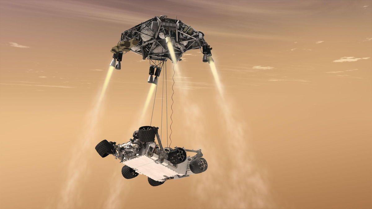 Rappresentazione artistica dello SkyCrane e del rover Perseverance con le ruote ancora ripiegate. Credits: NASA
